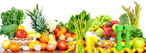 Vegetables fruits and dumbbells . Dieting and sport background.